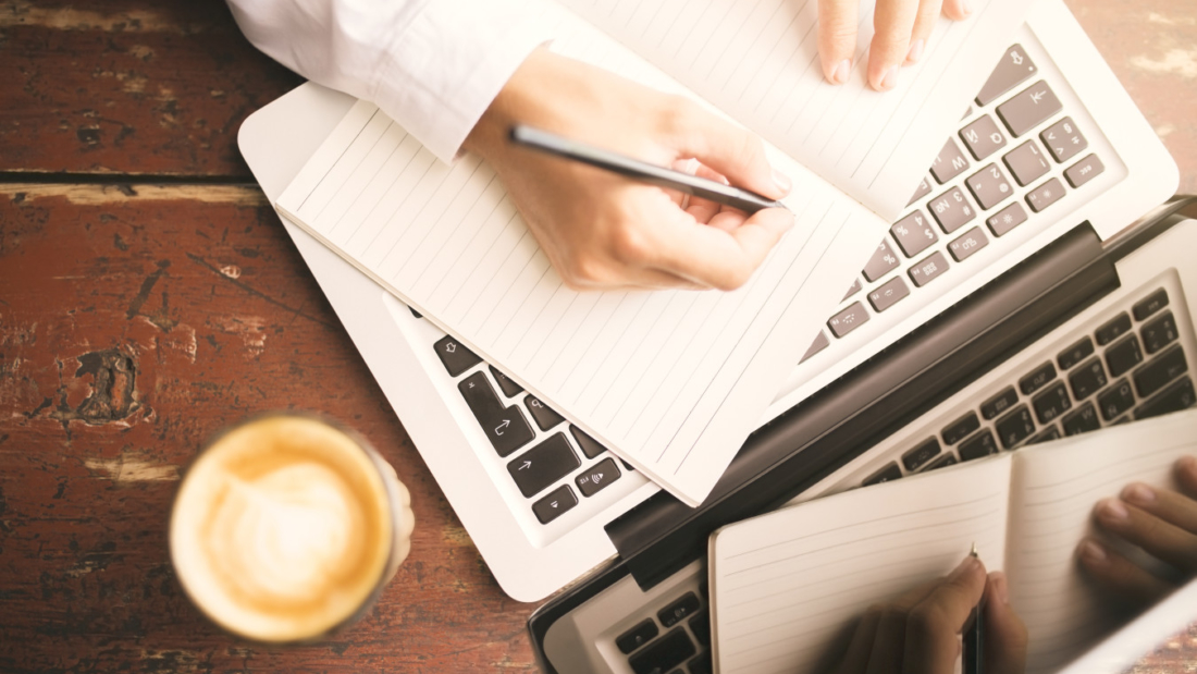 Man hands writing in the diary, coffee mug and laptop on wooden table