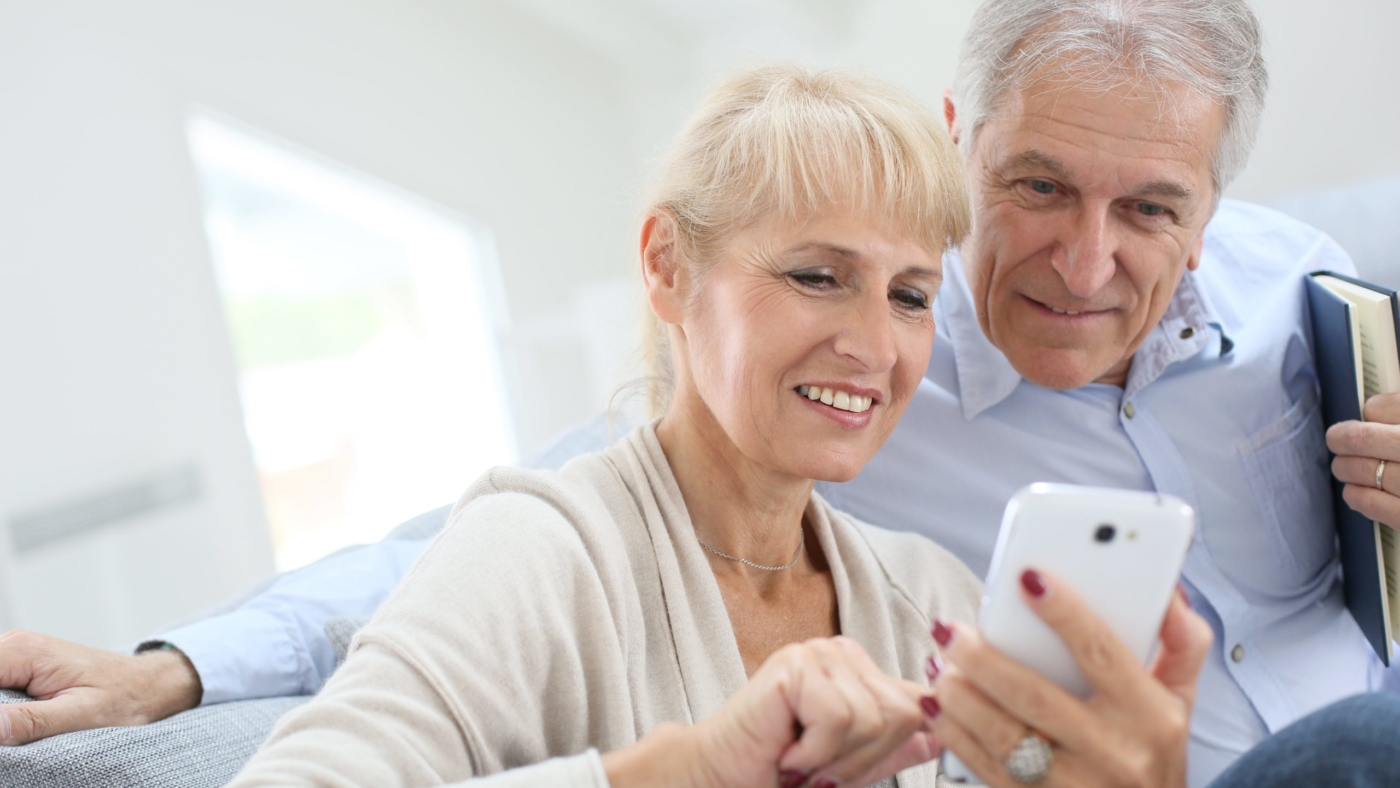 Mature adults look at smartphone