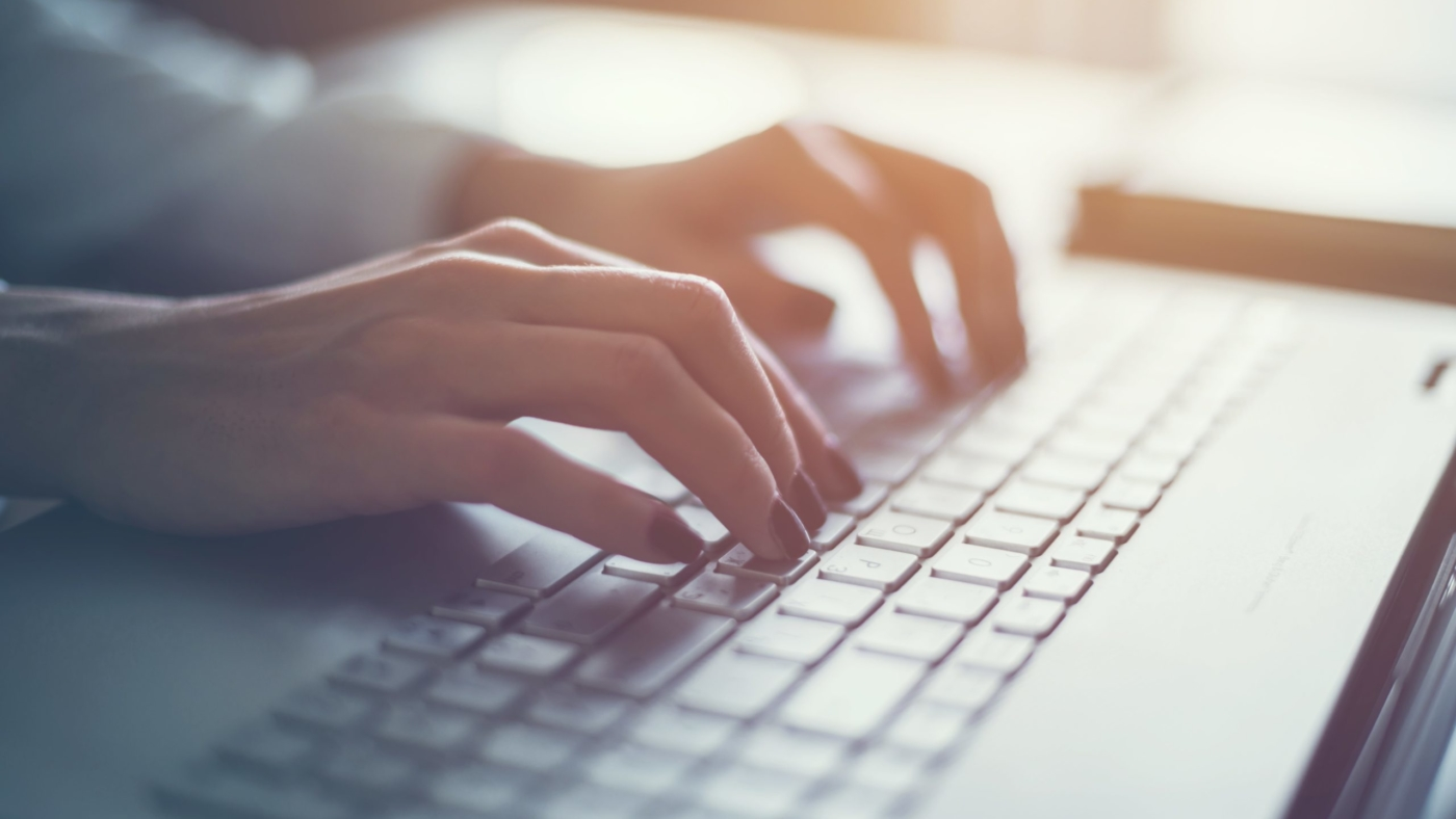 Woman writes a blog on her computer
