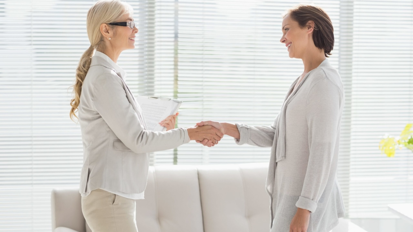 Hearing professional shakes patient's hand