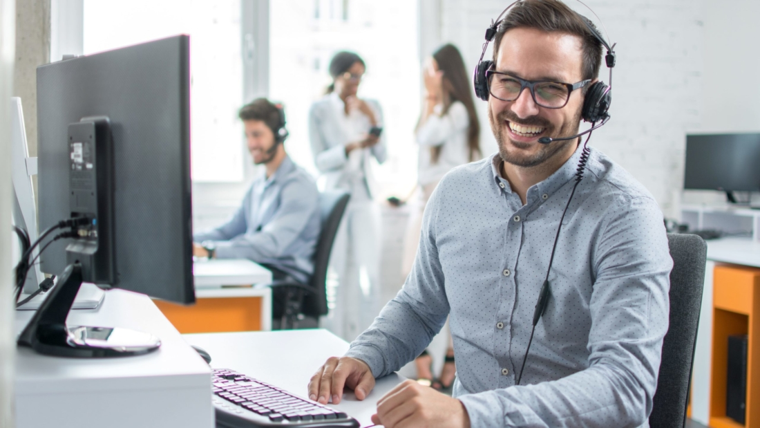 Tech support staff member smiles while on a call