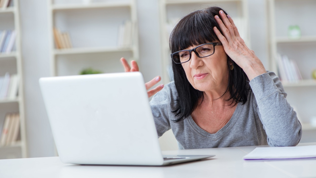 Frustrated woman looks at computer