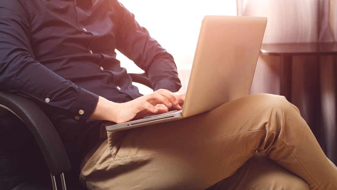 Man sitting with laptop on chair