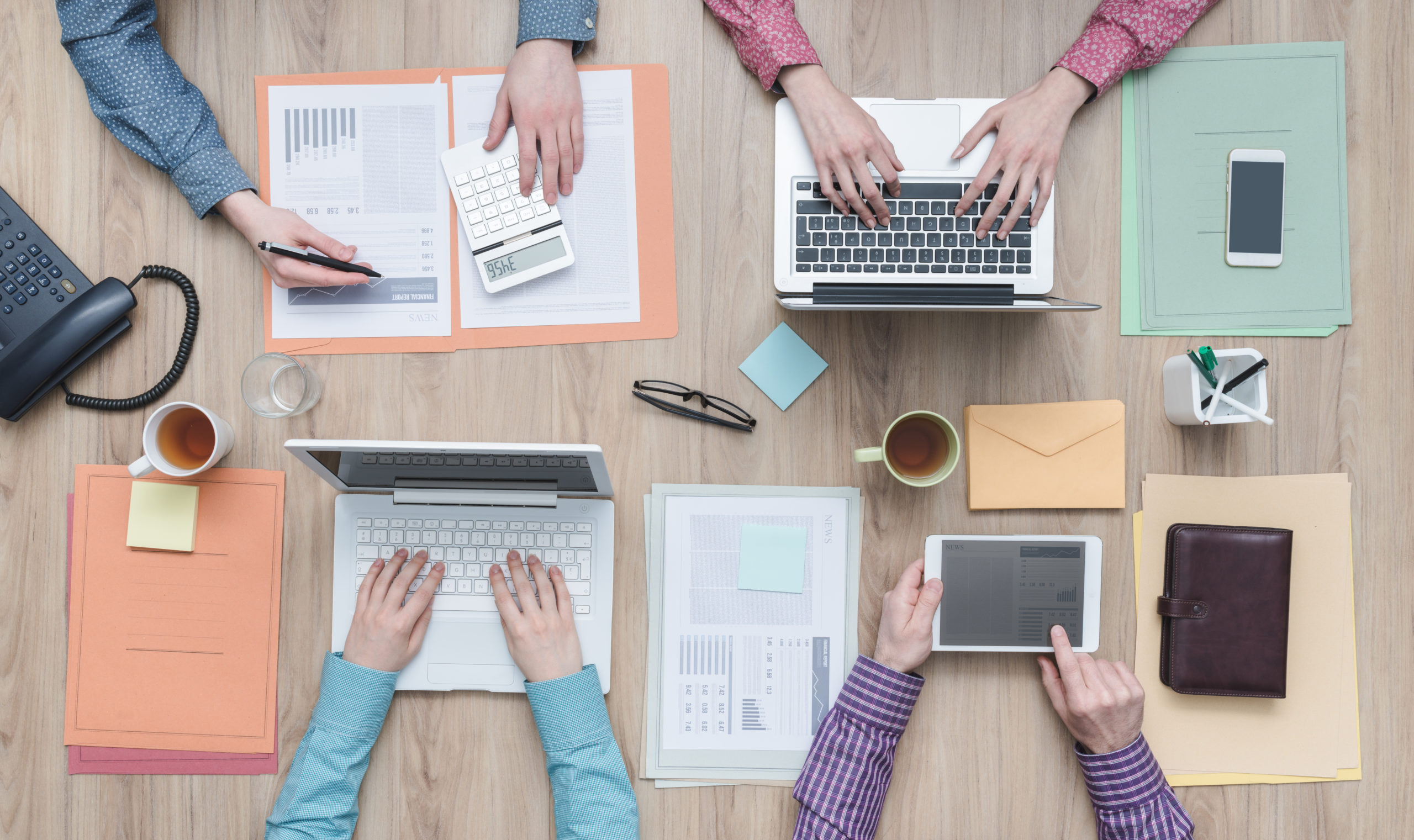 Business team working at office desk with laptops and financial reports, flat lay