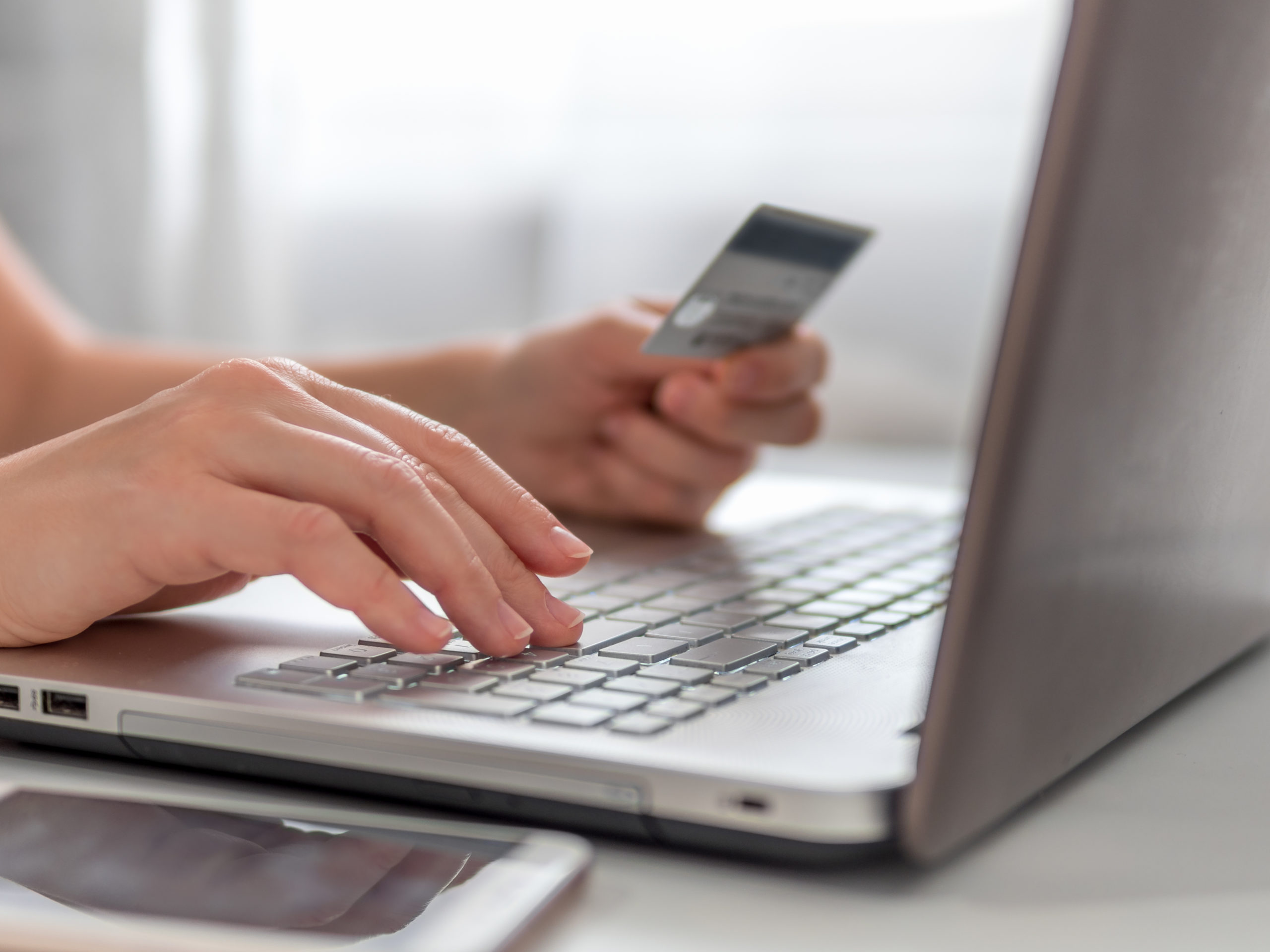 Online shopping concept. Close-up woman's hands holding credit card and using laptop keyboard for online shopping