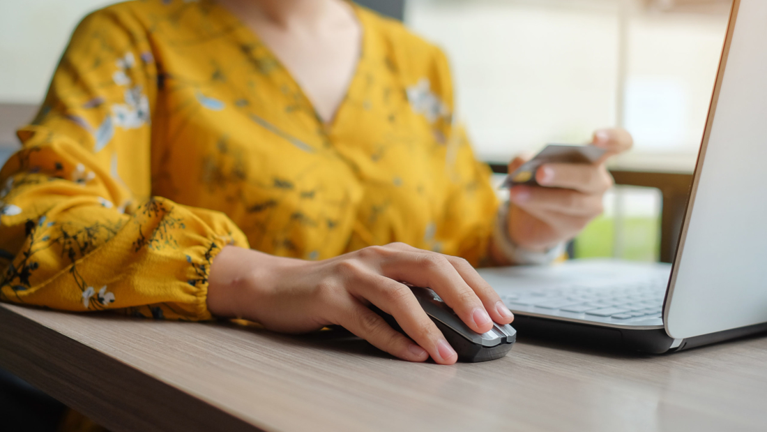 Asian woman holding credit card and using laptop for online shopping while making orders. internet, technology, ecommerce and online payment concept